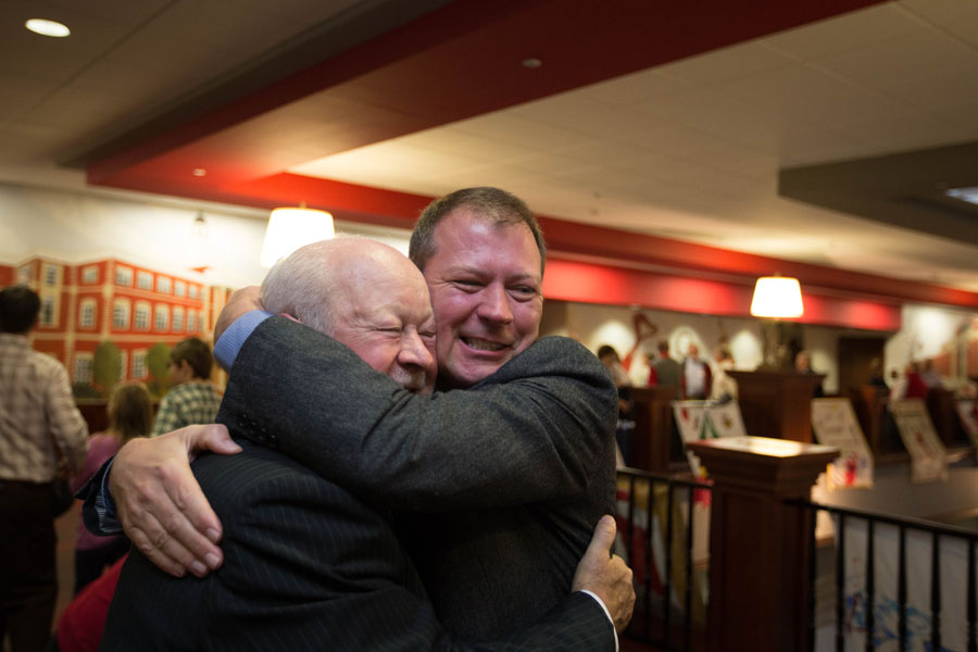 Chris Poynter (right) hugs former Student Publications Director Bob Adams.