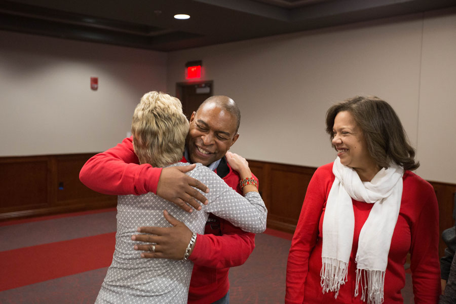 Thomas George (center) hugs Sherry West as Tamara George watches.