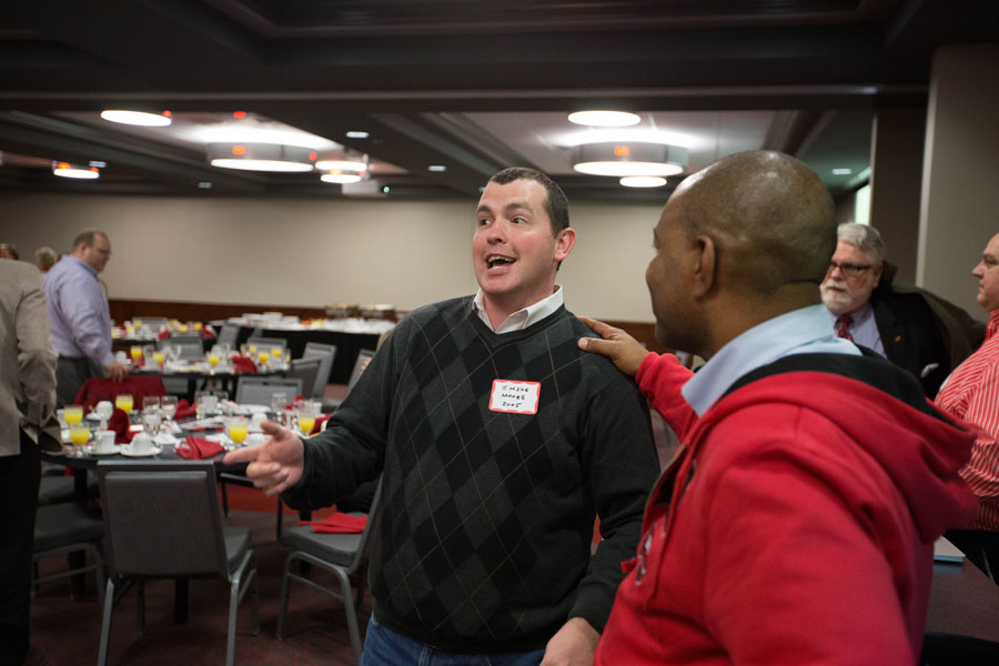 Alumni J. Michael Moore (center) and Thomas George share a laugh.